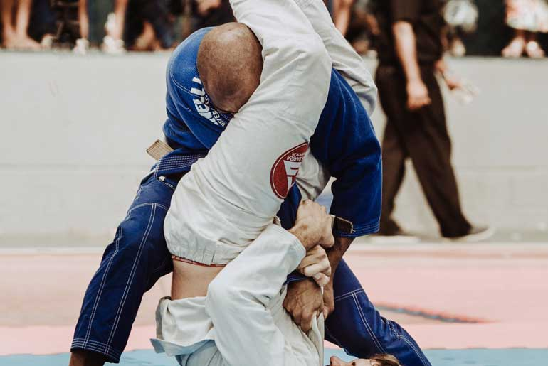 Man being arm barred in BJJ competition